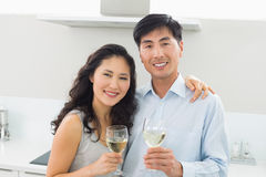 Loving young couple with wine glasses in kitchen Stock Photography