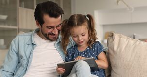 Dad spend time with little daughter relaxing together with tablet