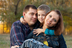 Loving young family in the autumn garden. Royalty Free Stock Image