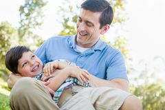 Loving Young Father Tickling Son in the Park. Loving Young Father Tickling Son in Outdoors at a Park Stock Images