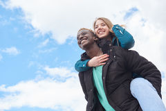 Loving Young International Couple on Sky Background. African Guy and Caucasian Woman Royalty Free Stock Photography