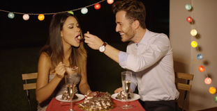 Loving young man feeding his girlfriend cake Royalty Free Stock Photography
