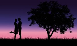 Loving young man and woman embracing on grass at tree under roma Royalty Free Stock Image