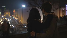 Loving young man and woman hugging gently, looking at romantic night city lights stock footage