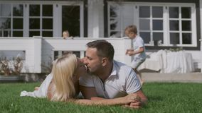 Loving mom and dad kiss lying on the grass near the house while the children run around them. Loving young mom and dad kiss while lying on the green grass near stock footage