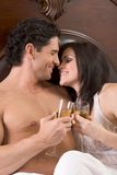Loving young sensual couple with Champagne in bed Stock Photography