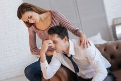 Loving young woman helping her depressed husband stock image