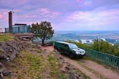 Lovos Tjeckien - Juli 05, 2017: grön jeepNissan överst kulle Lovos bredvid den turist- stugan med sikt till Pistany sjön, Rado Royaltyfria Foton