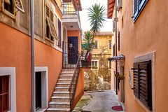 Lovran, Istria, Croatia. Vintage medieval buildings. Lovran, Istria, Croatia. Vintage buildings and houses at narrow lanes of old town. Stone stairs, wooden stock image