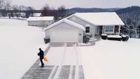 Low aerial view of homeowner shoveling show from driveway. A low angle aerial view of a homeowner shoveling snow from the driveway at a home in a typical stock video footage