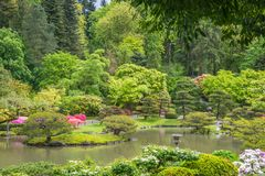 Spring Landscape of Japanese Garden with Pond, Stone Lantern, and Wooden Gate in the background. Stock Photos