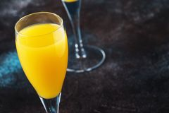 Low alcohol cocktail mimosa with orange juice and cold dry champagne or sparkling wine in glasses, blue background with flowers,. Place for text, selective stock photos