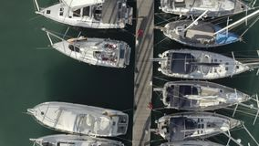 Low altitude aerial top down view of a marina pier and many docked sailboats. Low altitude aerial top down view of a marina pier stock footage