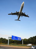 Low-altitude flight. Airplane during low-level flight over highway Stock Photos
