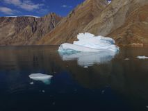 Low-altitude oblique drone image of an iceberg and its reflection in calm fjord waters with steep mountains in the background. Drone aerial image of an iceberg royalty free stock images