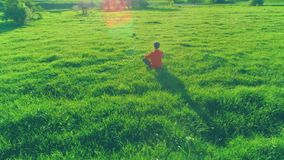 Low altitude radial flight over sport yoga man at perfect green grass. Sunset in mountain. UHD 4K aerial view. Low altitude radial flight over sport yoga man at stock video footage