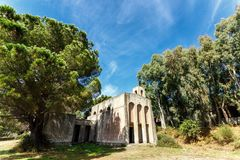 Low angle of abandoned religious building. Of white stone under beautiful huge trees in park or forest Royalty Free Stock Photos