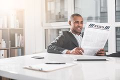 Young handsome man resting with journal. Low angle of african businessman sitting at office and reading newspaper. He is relaxed while concentrated. Copy space stock image