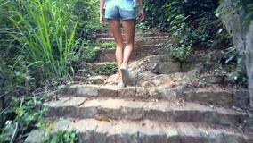 Low angle back shot girl walks along track in jungle. Low angle backside shot girl in denim shorts goes up stone steps through deep tropical jungle stock video