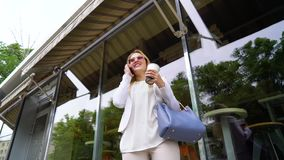 Low angle of business woman talking on smartphone during coffee pause outside. Low angle shot of young business woman talking on smartphone during coffee pause stock footage