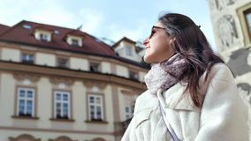 Low angle carefree woman tourist admiring amazing architecture building medium close-up. Smiling female traveler relaxing enjoying walking surrounded by stock footage