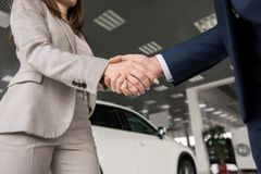 Car Salesman Shaking Hands with Client. Low angle close up of car salesman shaking hands with women buying new car in dealership showroom Stock Photography
