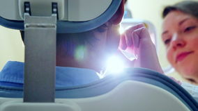 Low angle close up of female dentist turning on lamp and examining patient stock footage