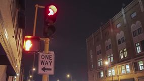 A low angle close up on a `one way` sign and traffic signal changing at night 4 k uhd timelapse. A timelapse of a traffic light changing at night in Minneapolis stock footage