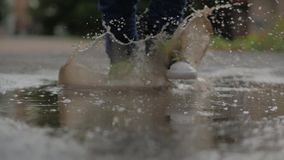 Low angle, close-up, unrecognizable kids running through puddles summer day after rain. Carefree children run in puddles stock video
