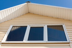 A low angle closeup view of roof upper floors of a house in daytime against blue sky. Royalty Free Stock Images