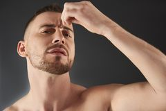 Low angle of concentrated frowning young bearded man plucking his eyebrows royalty free stock image