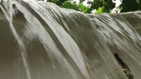 Low angle CU of a small manmade waterfall in tropical Southeast Asia stock video