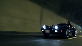 Low angle diagonal shot of Corvette driving through the tunnel stock video footage