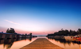 Low angle Dock on the Bay. A low angle perspective of an empty dock on the bay at a local marina with boats an storage units. Long exposure stock photography
