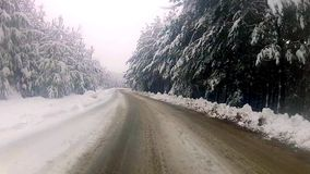 Low angle driving POV around S curve on snowy country road, timelapse stock footage