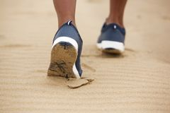Low angle female shoes walking in sand royalty free stock photos
