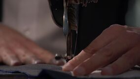 Low angle footage of a tailor sewing two cloths together on his sewing machine