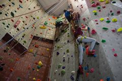 Low angle view of athletes and trainer climbing wall in club. Low angle full length of athletes and trainer climbing wall in club Royalty Free Stock Photo