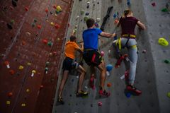 Low angle view of athletes and trainer climbing wall in gym. Low angle full length of athletes and trainer climbing wall in gym Stock Photography