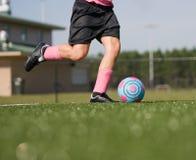 Low angle of girl kicking soccer ball Stock Photography