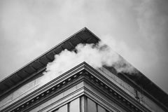 Low Angle and Gray Scale Photography of Building With a Smoke Stock Photography