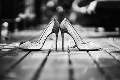 Low angle of high heels glitter women shoes place on the wooden floor in black and white. The Black and White of women glittering high heels shoes on the wooden stock image