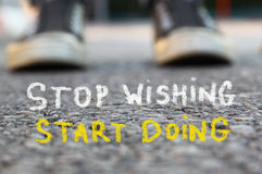 Low angle image of asphalt road and person sneakers with the text stop wishing start doing Royalty Free Stock Photography
