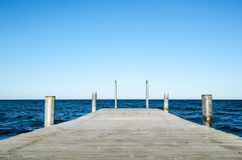 Low angle image of a wooden bath pier in blue water Stock Images