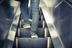 Low angle male feet walking in sneakers up escalator. Low angle male feet walking in sneakers up escalator vintage style Stock Photography