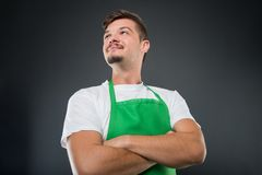 Low angle of male supermarket employer with arms crossed. On black background Stock Photos