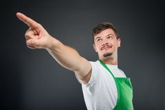 Low angle of male supermarket employer pointing up Royalty Free Stock Image