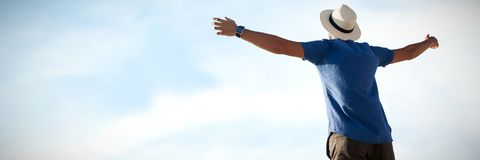 Composite image of low angle of a man raising arms up. Low angle of a man raising arms up  against blue sky with clouds Royalty Free Stock Image