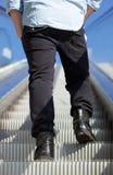 Low angle man standing on escalator Stock Photo