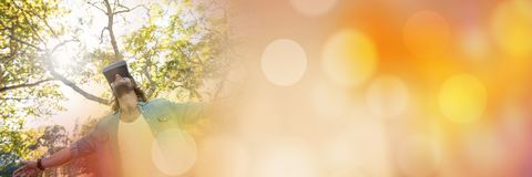 Low angle of man in virtual reality headset  embracing forest with orange bokeh transition Stock Photography